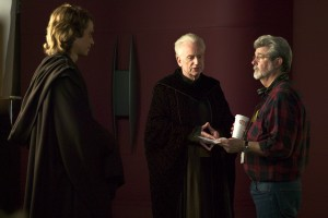 Actors Hayden Christensen (Anakin Skywalker) and Ian McDiarmid (Supreme Chancellor Palpatine) discuss a major scene in the Supreme Chancellor's office with director George Lucas. Photo by Merrick Morton.TM & © 2005 Lucasfilm Ltd. All Rights Reserved. Photo by Merrick Morton.